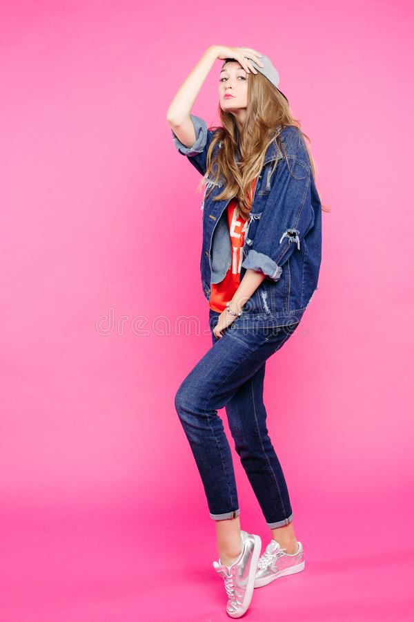 As calças de brim vestindo da menina à moda equipam a dança no estúdio foto de stock