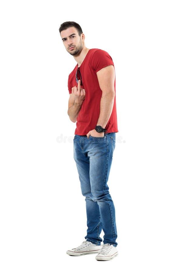 As calças de brim vestindo irritadas do homem novo e o t-shirt vermelho que mostram o dedo médio obsceno gesticulam imagem de stock