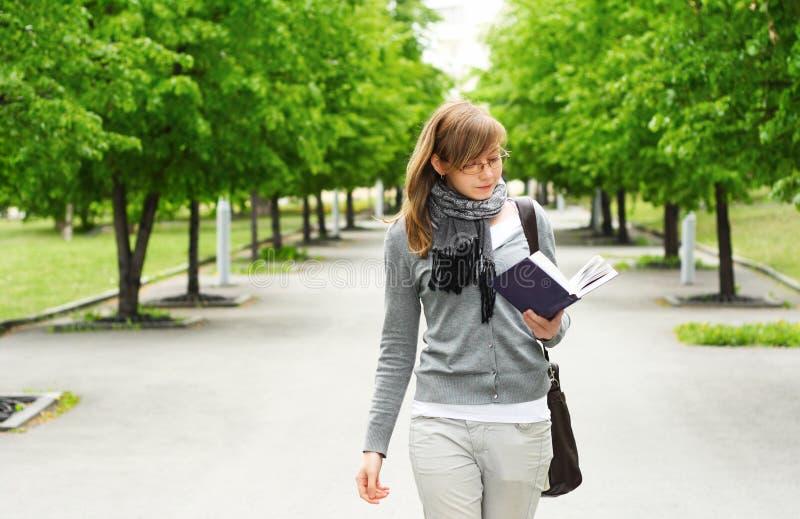 As caminhadas da menina, lendo o livro imagens de stock royalty free