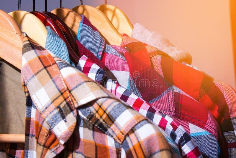 As camisas de manta do moderno penduram sobre na cremalheira da loja em um sto da roupa fotos de stock
