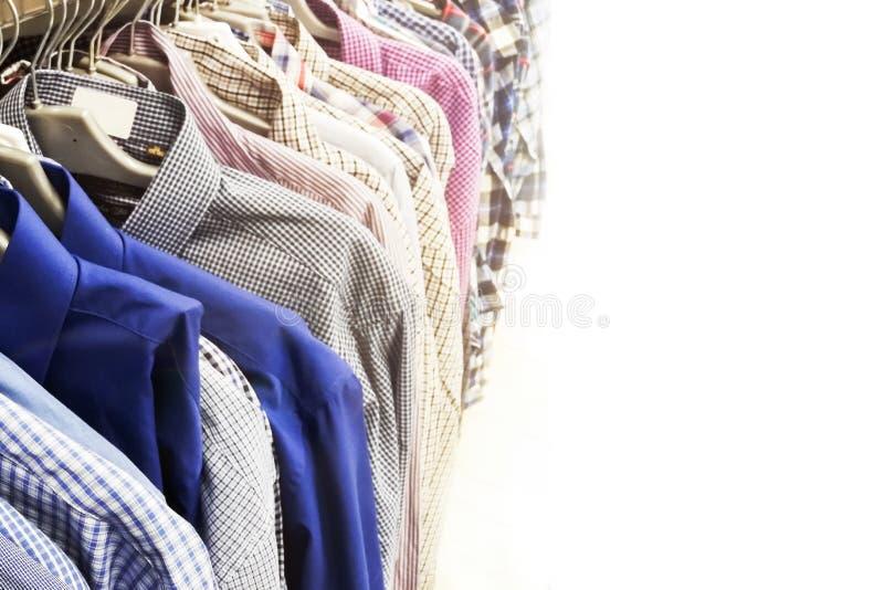 As camisas dos homens de cores diferentes em ganchos Foco seletivo Cópia do espaço imagem de stock royalty free