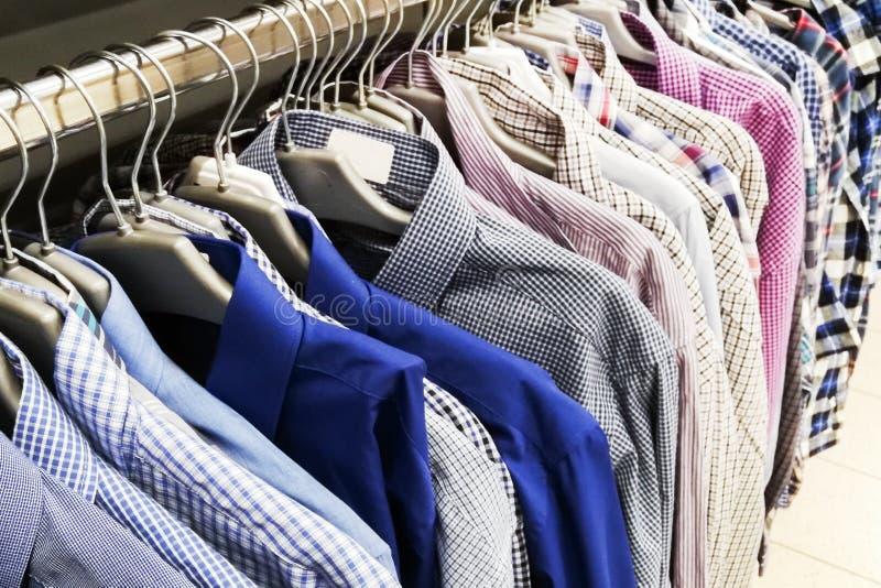 As camisas dos homens de cores diferentes em ganchos Foco seletivo Fim acima foto de stock