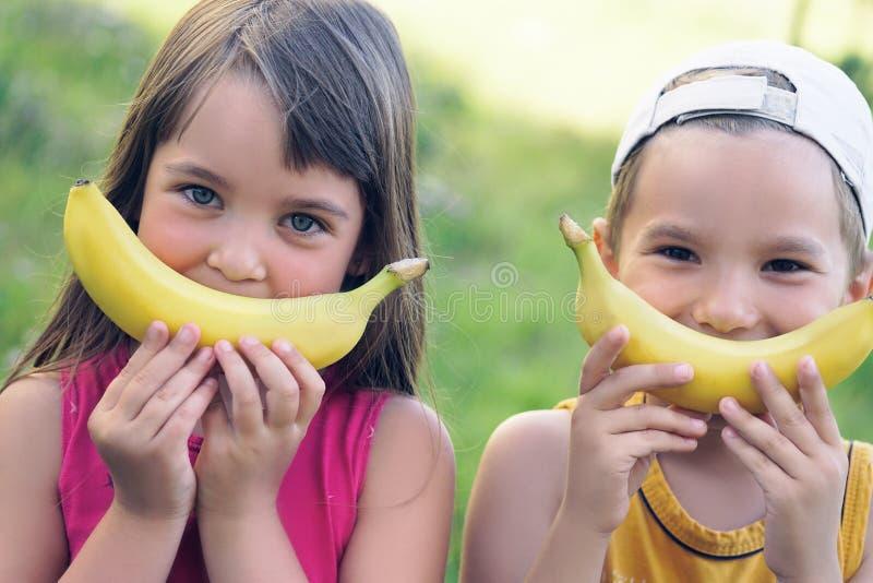 As caras de uma moça e de um menino bonitos com banana sorriem no fundo da natureza fotografia de stock royalty free