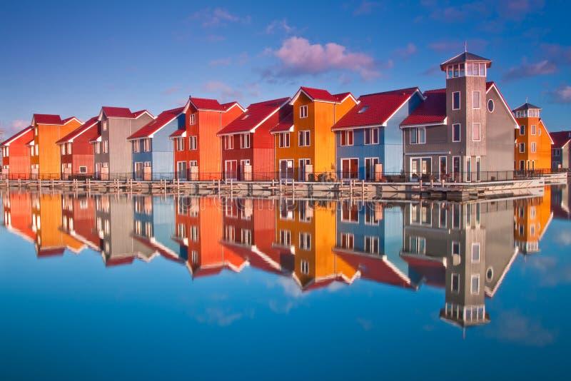 As casas de madeira coloridas aproximam a água imagens de stock