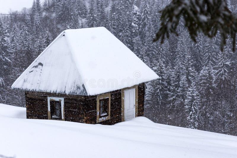 As casas de madeira pequenas em montanhas romenas no inverno temperam fotos de stock