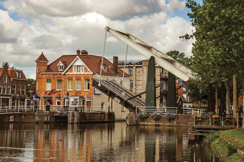 As casas e a ponte de bascule refletiram na superfície larga da água do canal no por do sol em Weesp foto de stock