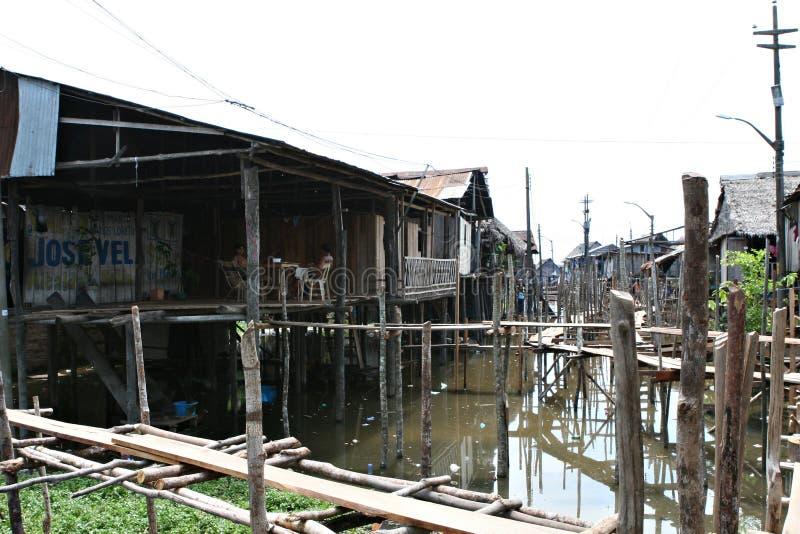 As casas em pernas de pau aumentam acima da água contaminada em Belen, Iquitos foto de stock