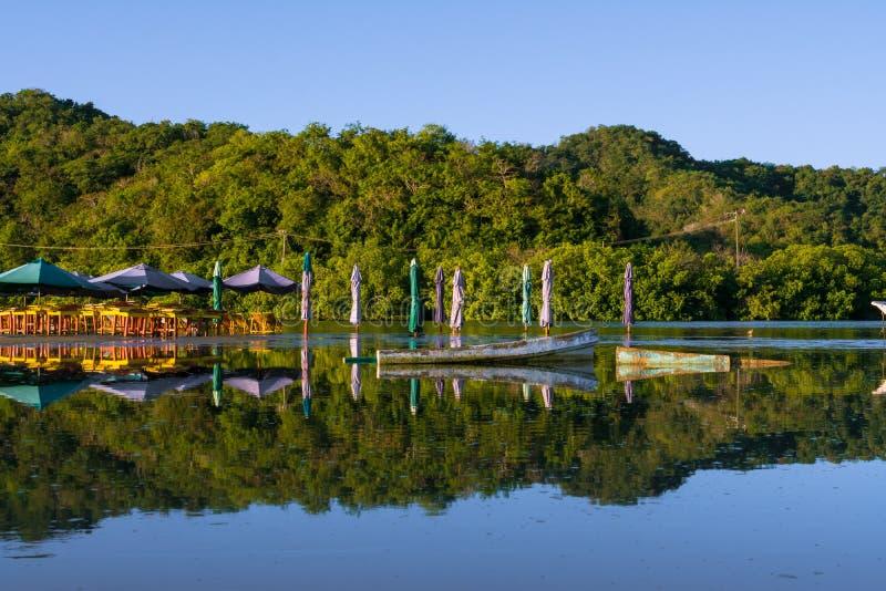 As casas, os guarda-chuvas e um barco são vistos na lagoa de Juluapan em Manzanillo Colima fotos de stock