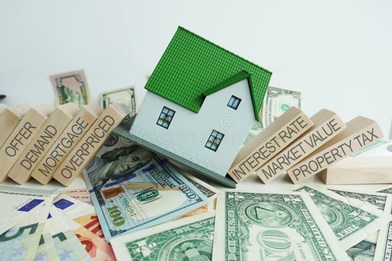 As causas da crise dos bens imobiliários com com a casa de queda em cédulas do dinheiro imagens de stock royalty free