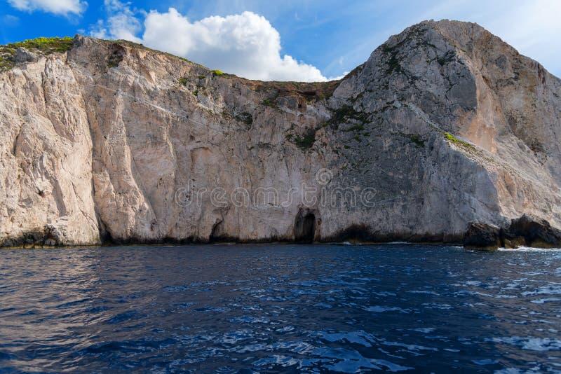 As cavernas azuis e a água azul do mar Ionian na ilha Zakynthos em Grécia e em sightseeing apontam Rochas no mar azul claro imagens de stock