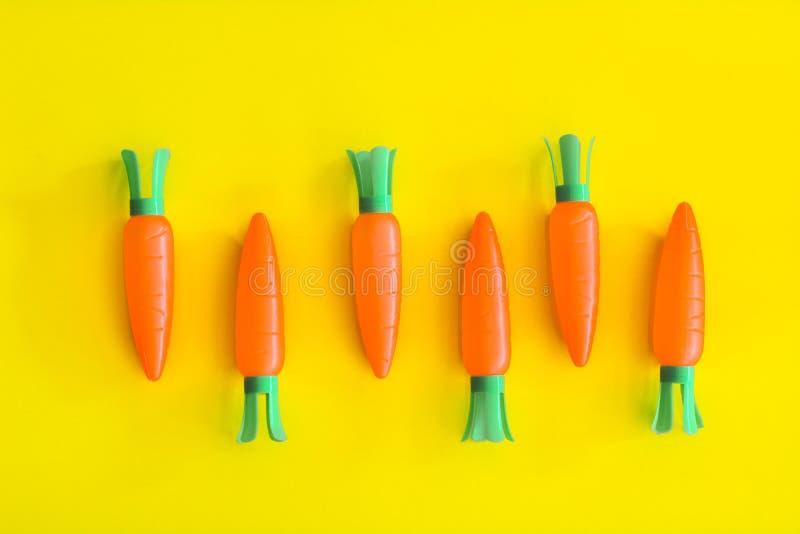 As cenouras abstraem o fundo amarelo mínimo, conceito do alimento imagem de stock