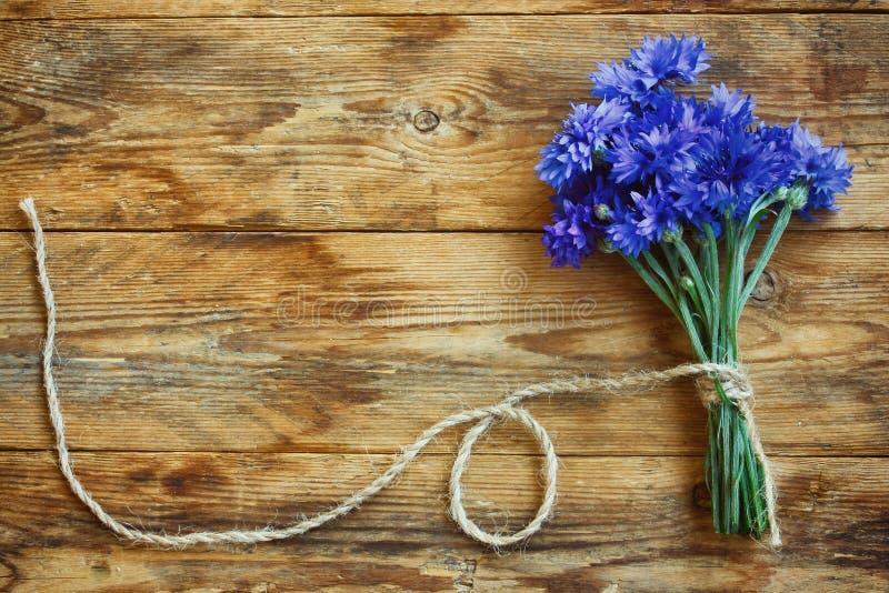 As centáureas do ramalhete do verão amarraram a corda na tabela de madeira fotos de stock