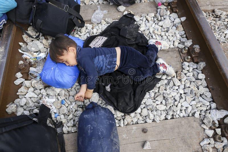 As centenas de imigrantes estão em uma espera na beira entre Greec imagens de stock