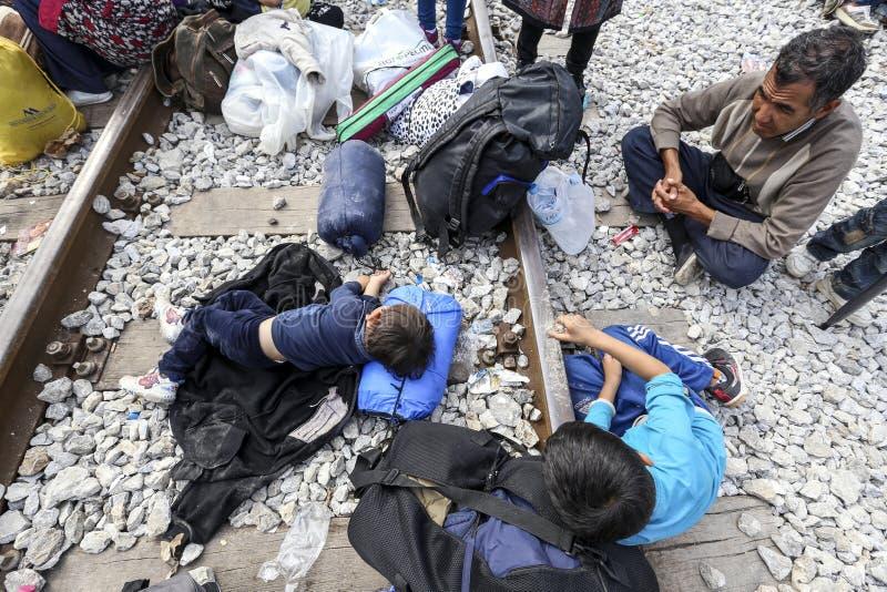 As centenas de imigrantes estão em uma espera na beira entre Greec fotos de stock royalty free