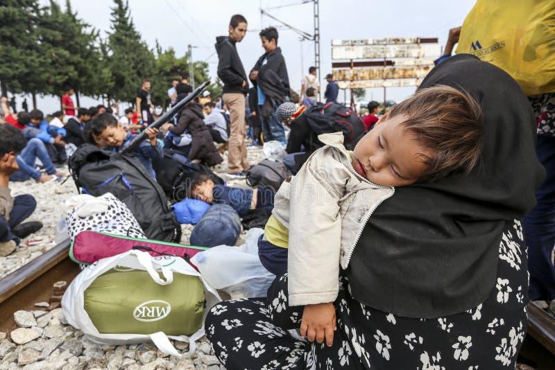 As centenas de imigrantes estão em uma espera na beira entre Greec imagem de stock