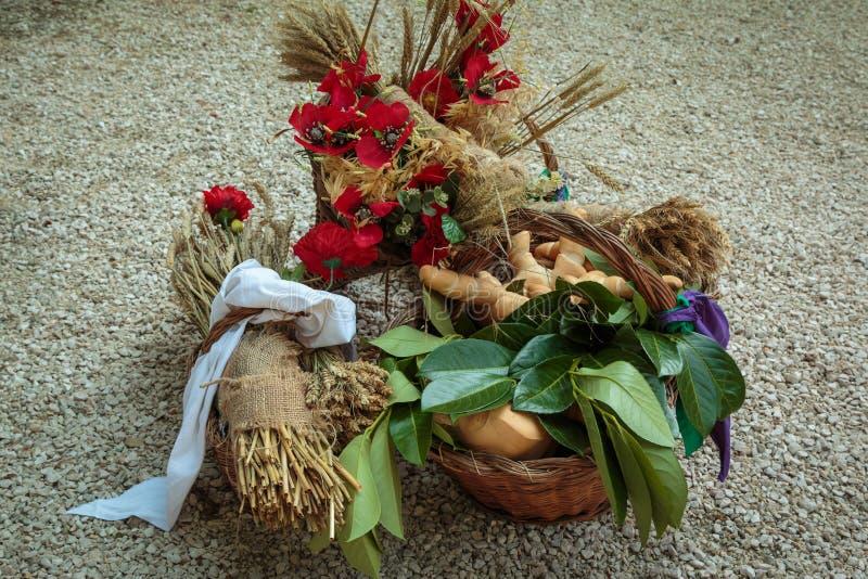 As cestas de vime encheram-se com o pão e as polias do trigo e do vermelho Flo foto de stock