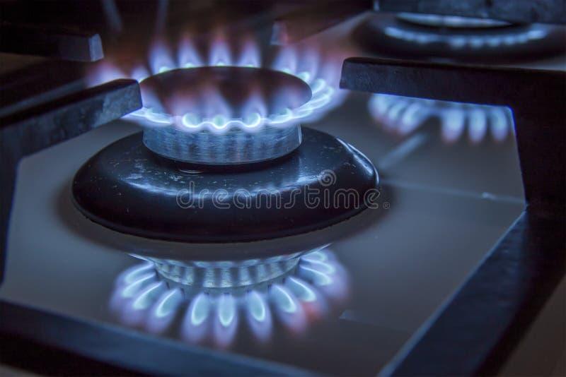 As chamas azuis do hob ardente do fogão de gás fecham-se acima na obscuridade em um blac fotos de stock royalty free