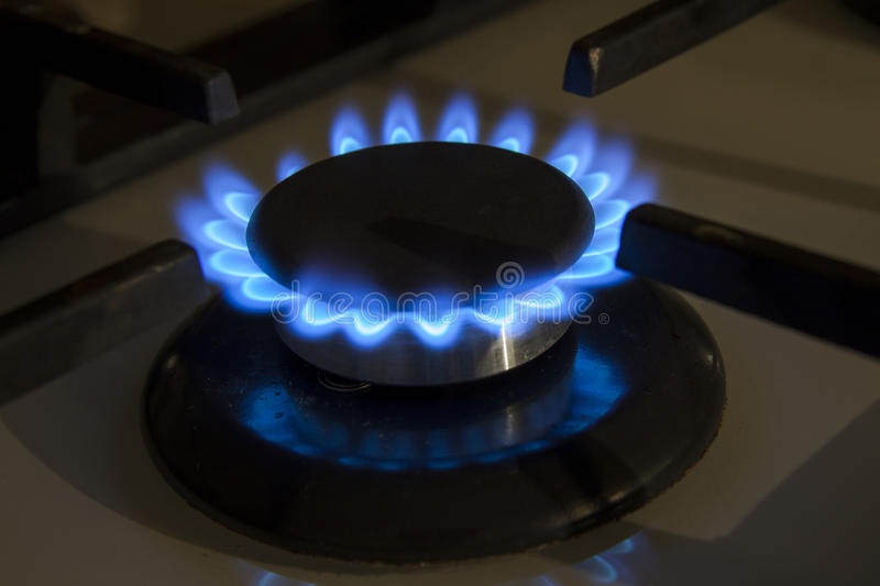As chamas azuis do hob ardente do fogão de gás fecham-se acima na obscuridade em um blac foto de stock