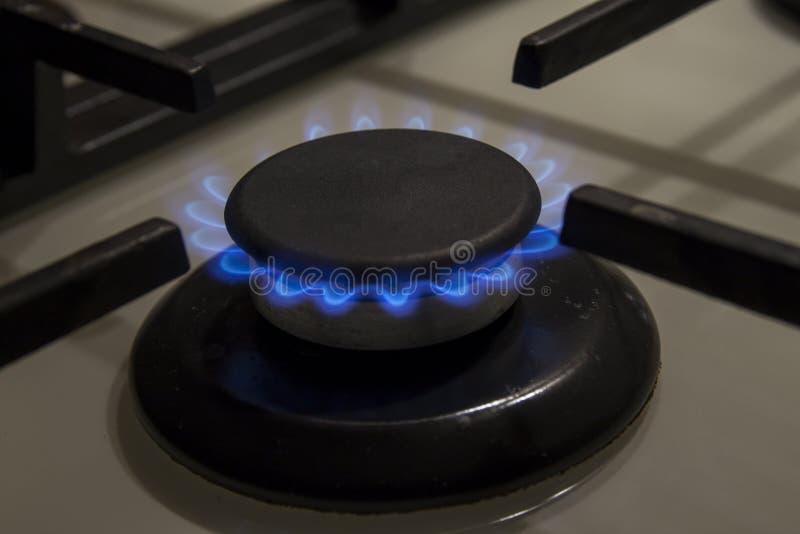 As chamas azuis do hob ardente do fogão de gás fecham-se acima na obscuridade em um blac imagens de stock royalty free