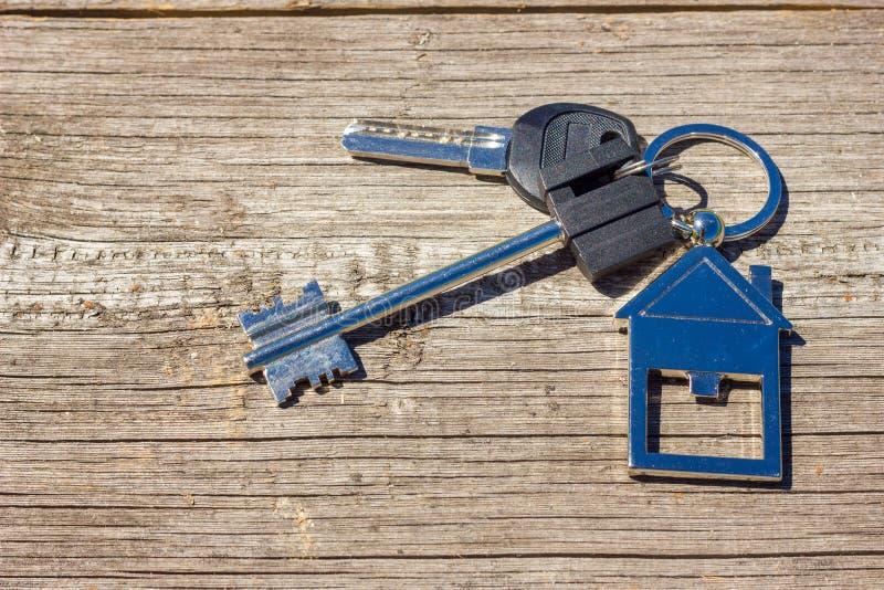 As chaves à casa encontram-se em um fundo de madeira, o conceito de comprar uma propriedade imagem de stock royalty free