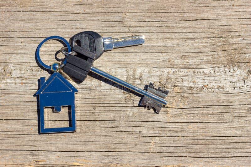 As chaves à casa encontram-se em um fundo de madeira, o conceito de comprar uma propriedade imagens de stock royalty free