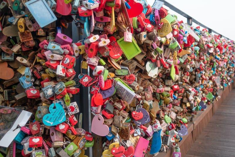 As chaves coloridas empilhadas de escrever os nomes de muitos pares são travadas na montanha namsan na torre de seoul imagem de stock