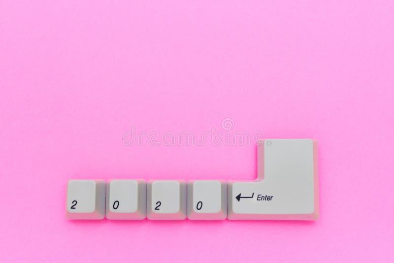 As chaves de teclado do computador com 2020 entram escrito usando os botões brancos no fundo cor-de-rosa Conceito da tecnologia d foto de stock royalty free