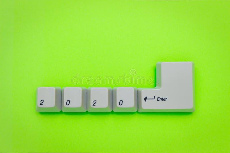 As chaves de teclado do computador com 2020 entram escrito usando os botões brancos no fundo verde Conceito da tecnologia do ano  imagens de stock