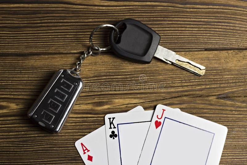 As chaves dos cartões e do carro de jogo em um fundo de madeira jogam imagem de stock