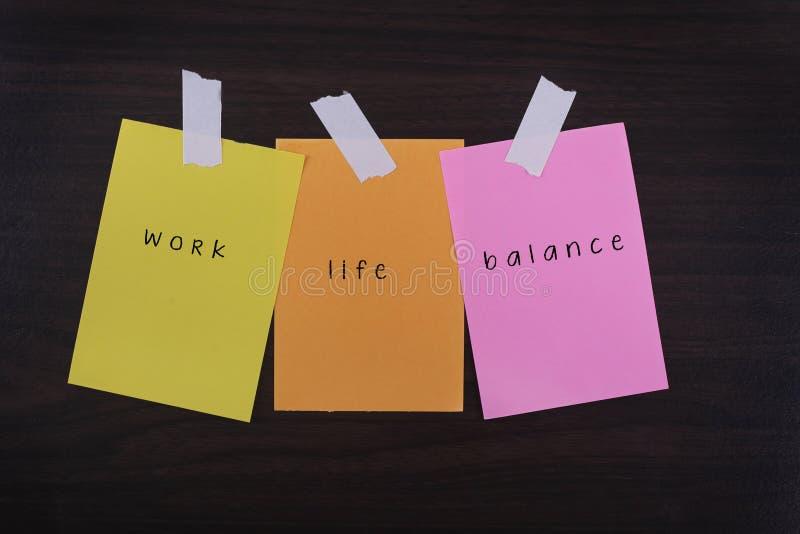 As citações da palavra da vida do trabalho equilibram em papéis pegajosos coloridos contra o fundo textured de madeira foto de stock royalty free
