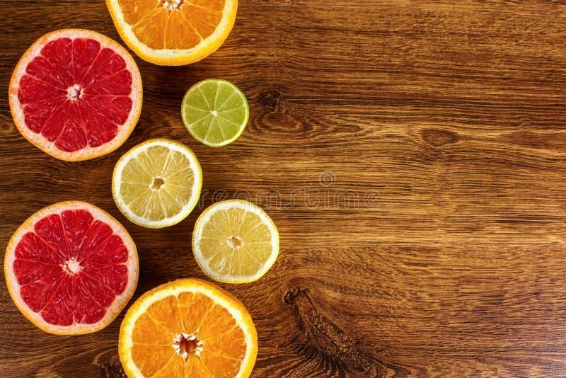 As citrinas cortaram laranjas do fundo, limões, cais, toranja em um fundo de madeira foto de stock