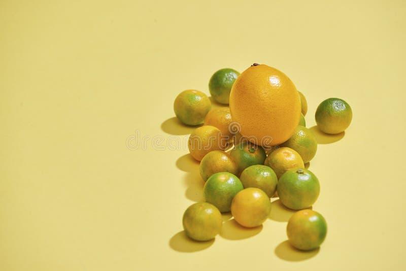 As citrinas estão em um claro - fundo amarelo O Kumquat, limão, o mandarino, laranja está em um fundo amarelo - imagem fotos de stock