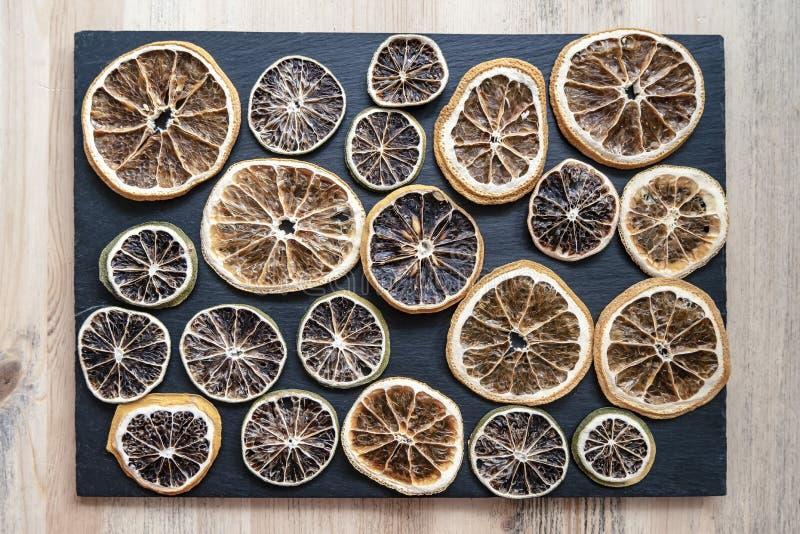 As citrinas secadas limão, cal e laranja para a decoração estão em uma placa escura da ardósia, em uma tabela de madeira wallpape imagem de stock
