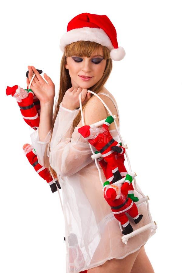 As cláusulas de Santa escalam acima da menina 'sexy' de Santa fotos de stock