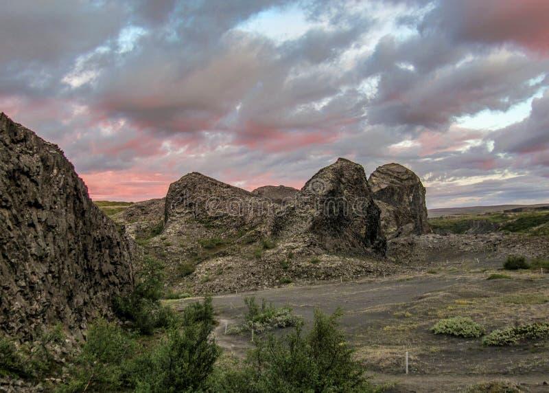 As colunas do basalto criam formações originais em Vesturdalur, Asbyrgi, com o céu dramático no por do sol, ao nordeste de Islând foto de stock royalty free