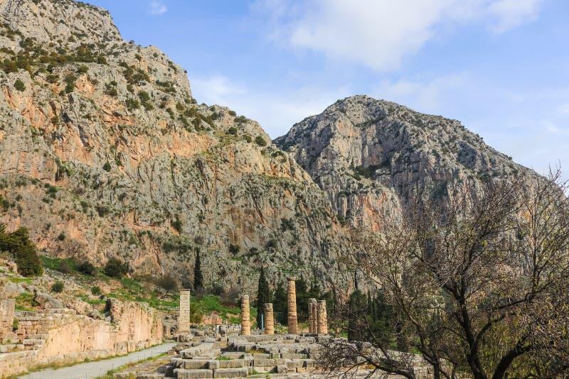 As colunas do templo de Apollo empequeneceram pela montanha no local arqueológico da montanha de Delphi Greece imagens de stock