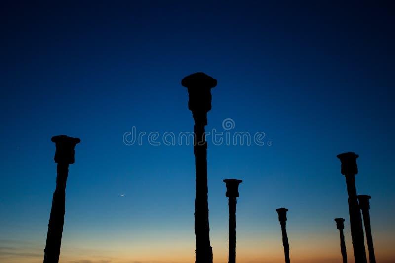 As colunas entram o suporte com opinião do por do sol na praia de Tedys foto de stock