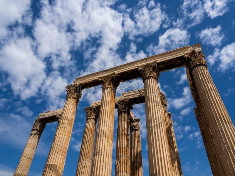 As colunas permanecendo do templo do olímpico Zeus em Atenas, Grécia dispararam contra o céu azul e nuvens pitorescas imagens de stock royalty free