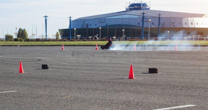 As competições de Karting, motorista karting conduzem um kart na perspectiva de uma construção moderna, muito fumo, vencedor, ave imagem de stock royalty free