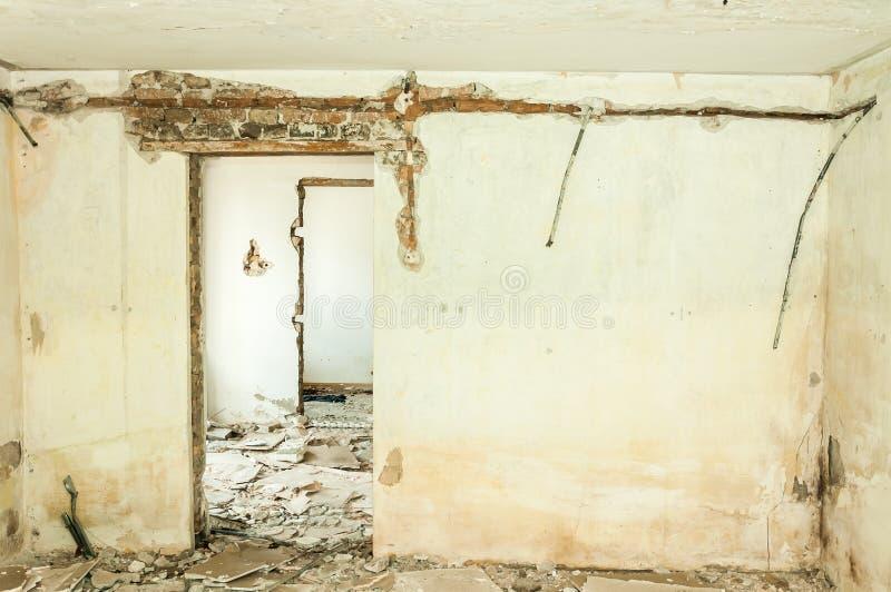 As consequências abandonaram e destruíram o interior da casa com paredes danificadas e as portas quebradas completamente dos tijo fotografia de stock