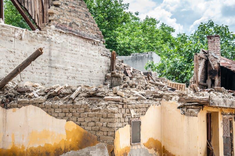 As consequências danificaram e desmoronaram telhado na casa arruinada com quadro da construção e a parede de tijolo de madeira foto de stock