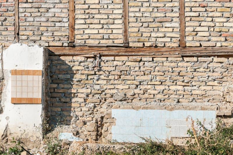 As consequências permanecem da casa desmoronada velha com o telhado quebrado e danificado com a parede de tijolo após o desastre imagens de stock