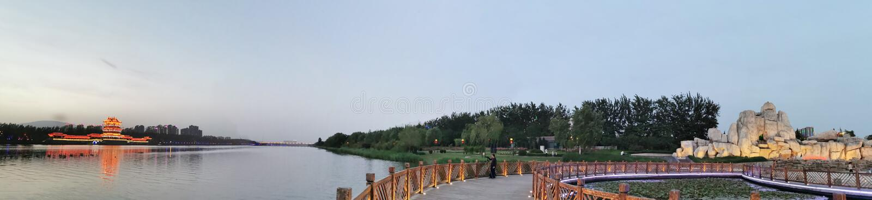 As construções antigas na distância, as madeiras, o jardim ornamental na vizinhança, o lago imagens de stock royalty free