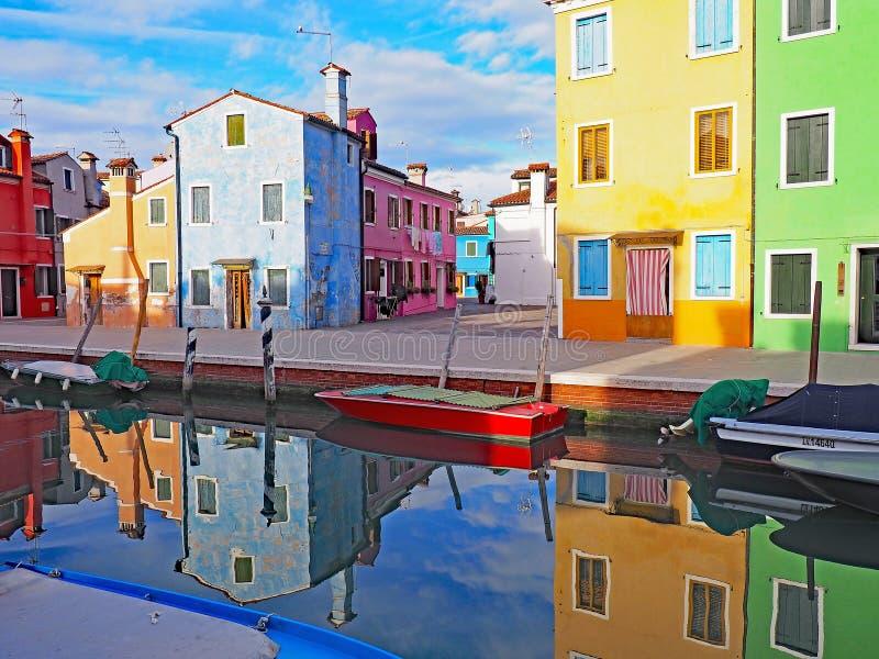 As construções coloridas refletem no canal na ilha de Burano em Itália fotografia de stock