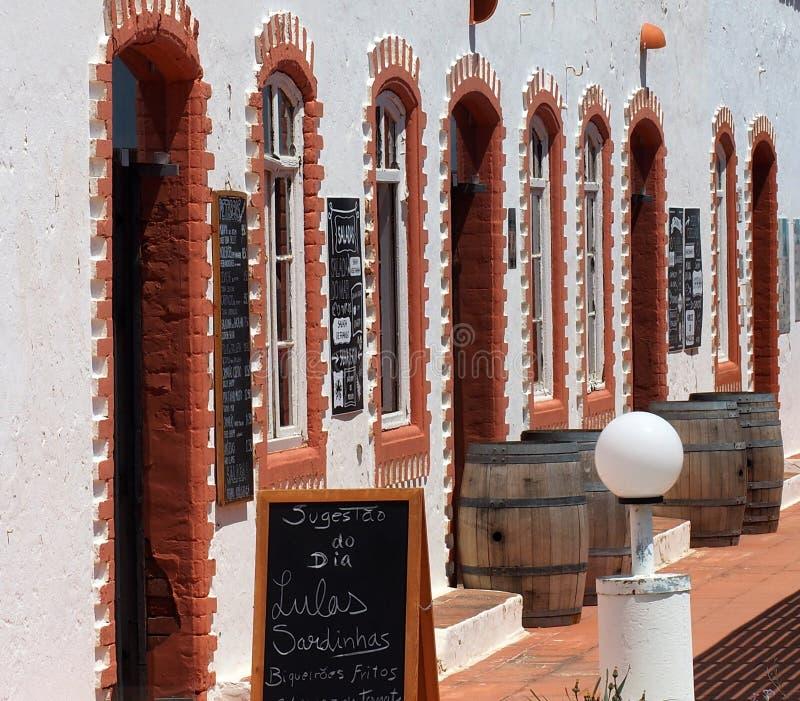 As construções lavadas brancas com a decoração do tijolo vermelho no Praia fazem Barril Tavira Portugal imagens de stock royalty free