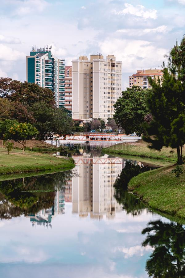 As construções refletiram na água de um rio, no P ecológico fotografia de stock