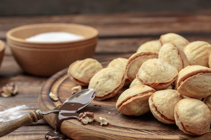 As cookies caseiros deram forma a porcas com leite condensado fervido creme na tabela de madeira imagem de stock