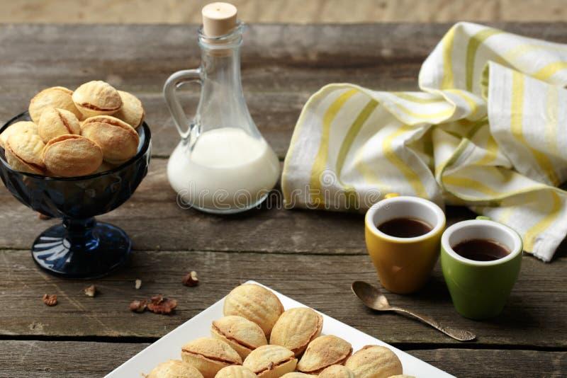 As cookies caseiros deram forma a porcas com leite condensado fervido creme na tabela de madeira Estilo rústico foto de stock royalty free