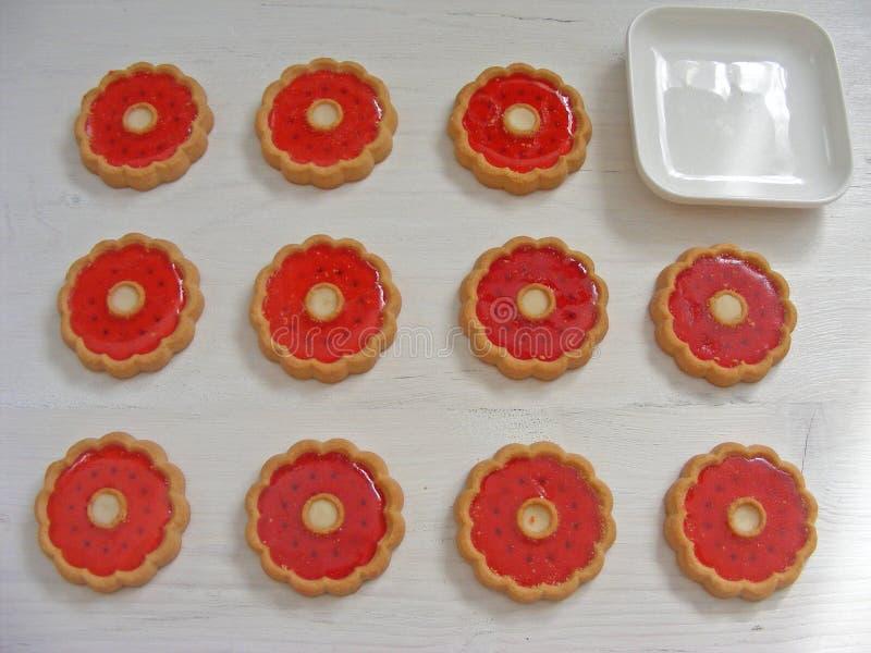 As cookies com geleia vermelha florescem para dentro no fundo branco foto de stock