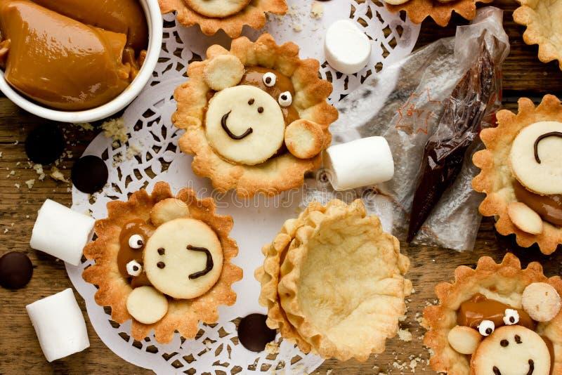 As cookies da preparação deram forma à cara do macaco, ingredientes e terminaram-na fotos de stock